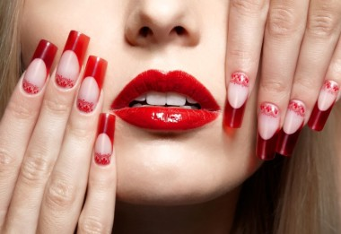 Fingers with red french acrylic nails manicure and paiting